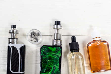 Still life with vape devices on the wooden background.