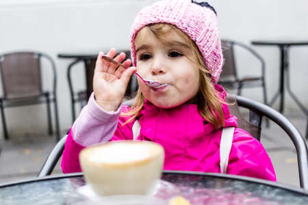 Portrait of a cheerful little girl sitting on the street in city cafe with mom and fooling around with coffee.