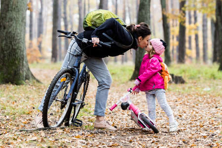 Mother giving a kiss to her daughter while riding bicycles.