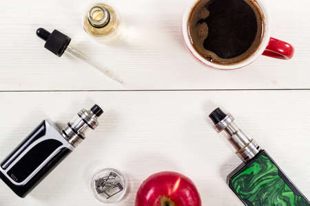 Still life with vape devices and coffee on the wooden background.