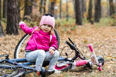 Adorable girl playing with a bike on beautiful autumn day Reklamní fotografie