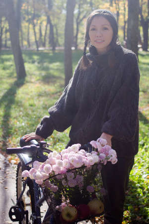 Happy young woman with bicycle relaxing in the park.