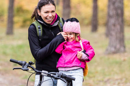 Happy mother and daughter riding bicycles in autumn park.
