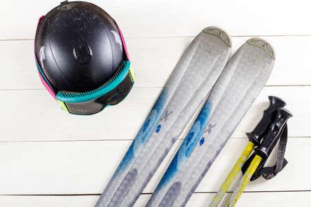 Overhead view of ski accessories placed on rustic white wooden table. Items included ski, goggles, helmet and ski sticks. Winter sport leisure time concept. Banque d'images