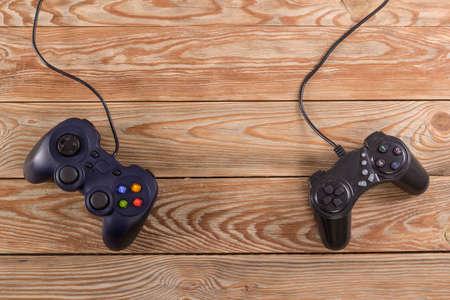 Retro computer gaming controllers placed on wooden background. Home video games time concept.