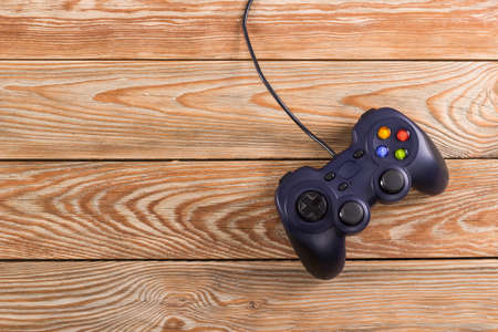 Retro computer gaming controller placed on wooden background. Home video games time concept.