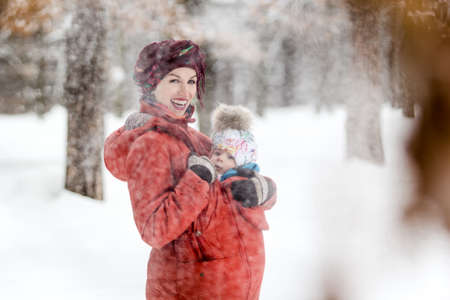 Mother carrying her baby girl wears red jacket and sling. Outdoor family fun time in winter, Stock Photo