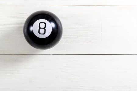 Magic prediction eight ball on white wooden background.