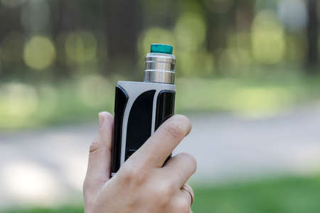 Vaping device in the man's hand. Electronic cigarette and vape concept. Quit smoking.