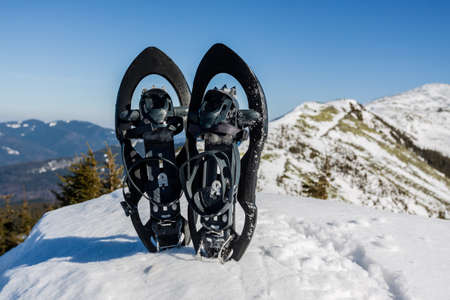 Winter hiking in the mountains. Black snowshoes in fresh show with snowflakes, at mountain view. Stock fotó
