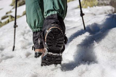 Man hiking with trekking poles. Equipment for walking on snow close up. Journey through the mountains in winter. Shoes for travel.