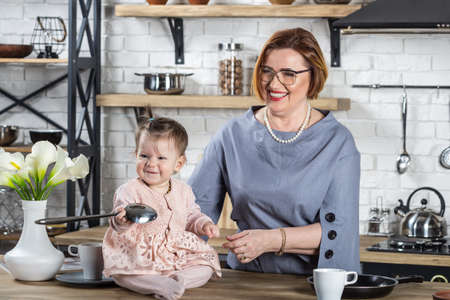 Beautiful grandma and granddaughter having fun at kitchen. Family cooking time. Stockfoto