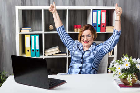 Smiling attractive senior businesswoman wearing glasses, working with phone and laptop in modern office. Happy aged teacher and successful woman company boss.