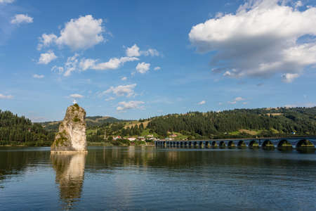 View at viaduct and river on a mountain valley with Piatra Teiului lime stone, Bicaz Lake in Romania Banco de Imagens