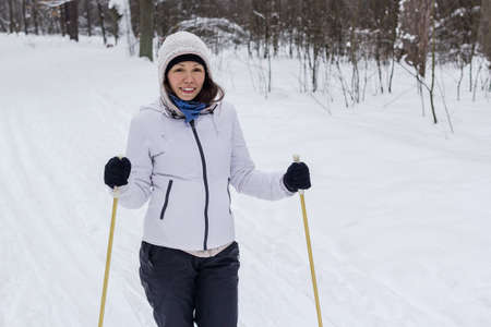 A woman at cross-country skiing in the winter forest.