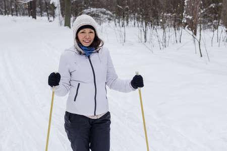 Una mujer en el esquí de fondo en el bosque de invierno.