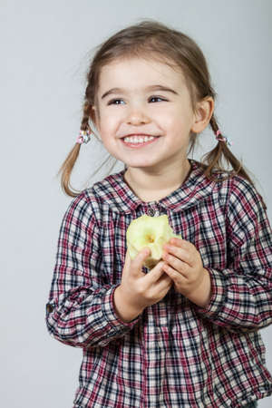Happy little girl having fun and eating apple on gray background.