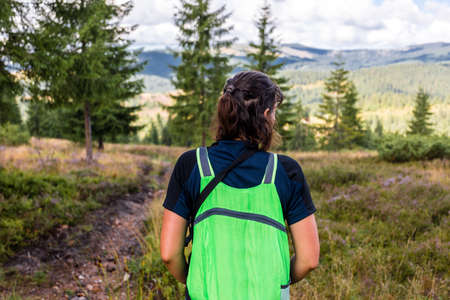 Young traveler woman with backpack looking forward at amazing mountains and valley view.