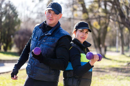 Strong and powerful people are working out outside in park. They are doing abs exercises. Young man and woman look serious and cocnentrated.