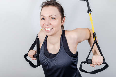 Upper body exercise concept.   beautiful woman exercising  suspension straps alone in studio.  concept isolated on white background.