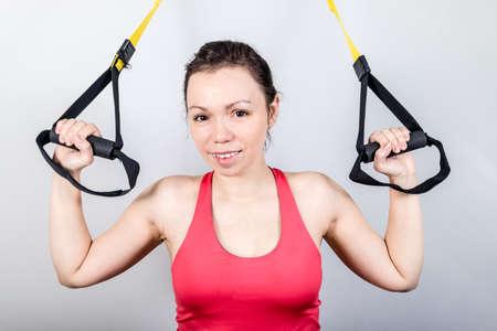Upper body exercise concept.   beautiful woman exercising  suspension straps alone in studio. 版權商用圖片