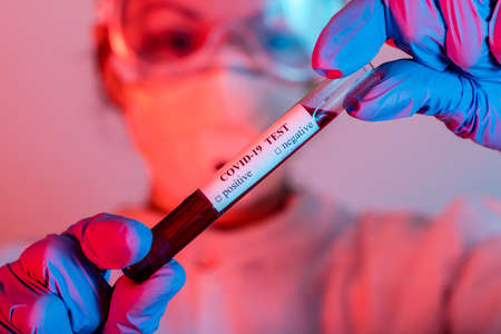 Doctor in protective wear holding test tube with blood for Coronavirus COVID-19 analyzing.