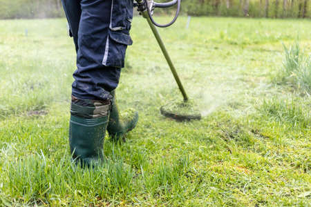 Young worker mowing lawn with grass trimmer outdoors in garden. Photo of maintenance professional worker cutting ground grass