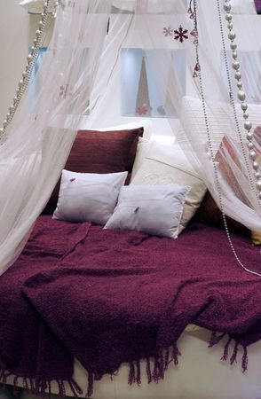 coverlet: Round bed with pillow by coverlet, transparent blind and decorations
