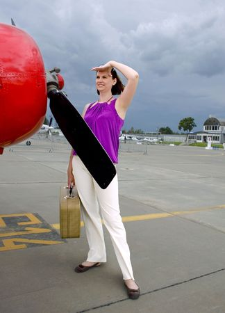 valise: Young woman with valise around airplane