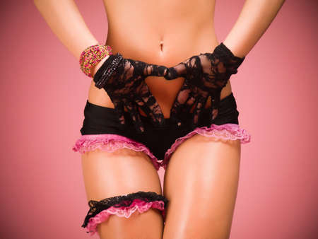Torso and hips of a female dancer wearing black and pink lace lingerie