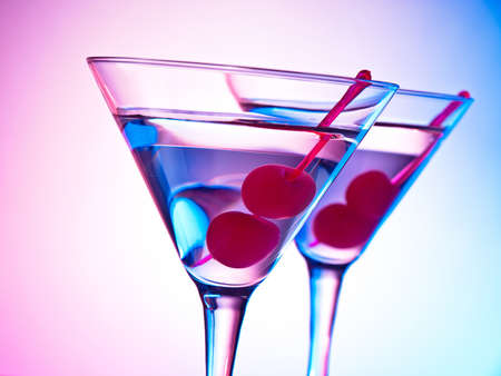 Two glasses of martini with red cherries on a mixed color background Stock Photo - 12974466