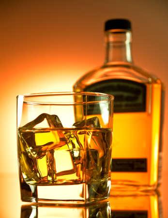Glas Whiskey on the rocks mit einer Flasche im Hintergrund Standard-Bild - 13589503