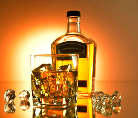 whisky bottle: Glass of whiskey on the rocks with a bottle in the background