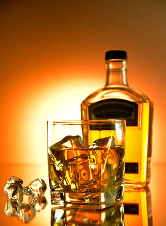 Glass of whiskey on the rocks with a bottle in the background photo