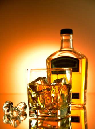 botella de whisky: Vaso de whisky en las rocas con una botella en el fondo