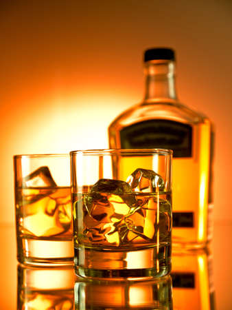 icecube: Two glasses of whiskey with a bottle in the background Stock Photo