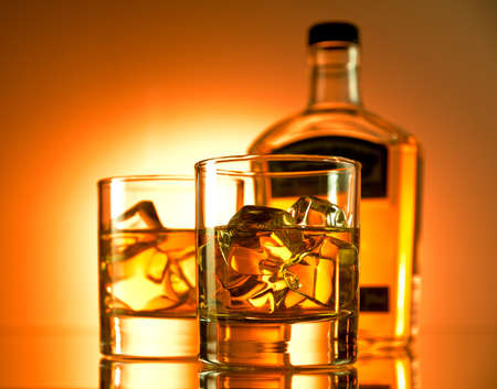 whiskey bottle: Two glasses of whiskey with a bottle in the background Stock Photo