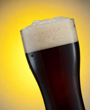 cerveza negra: Vaso de cerveza negra sobre fondo amarillo