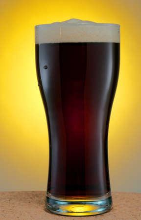 Glass of dark beer over yellow background photo