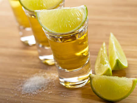 Three shots of tequila with lime and salt Stock Photo