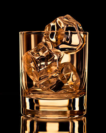 whisky glass: Empty whiskey glass with ice cubes on black background