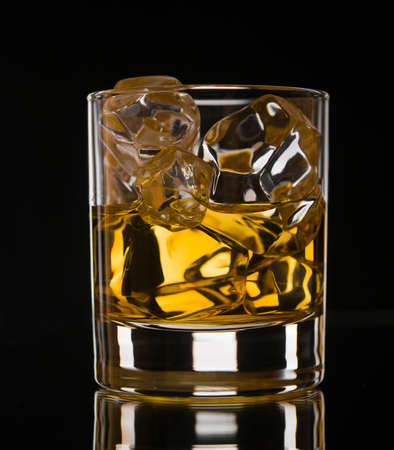 Glass of whiskey on the rocks on black background