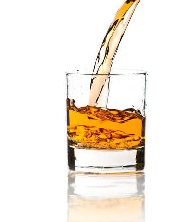 whisky: Pouring whiskey in a clear glass, on white background Stock Photo