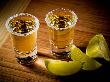 Two shot glasses of tequila with a rim of salt, and lime wedges