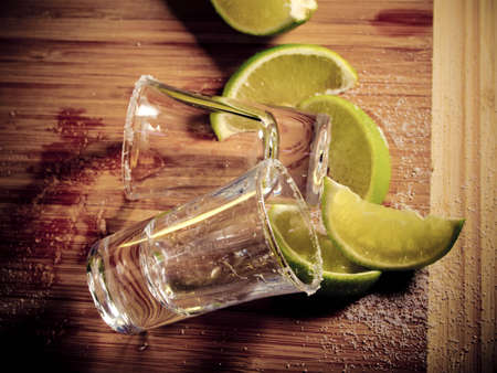 Two empty shot glasses left from tequila, wedges of lime, and salt