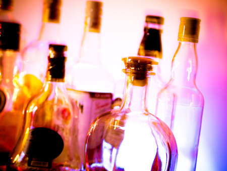 Various bottles at a bar arragged in rows Standard-Bild
