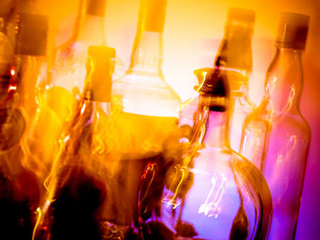 corked: Various bottles at a bar arragged in rows, motion blur