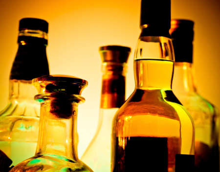 Row of bottles at a bar  over yellow background Standard-Bild