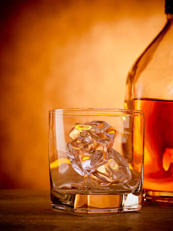 scotch whisky: Bottle of whiskey with an empty glass waiting to be filled