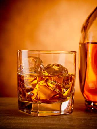 botella de licor: Vaso de whisky en las rocas junto a una botella Foto de archivo